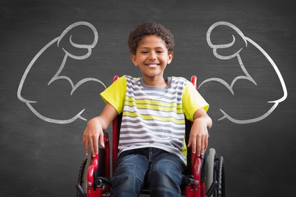 Image of disabled pupil smiling with illustration of muscles on wall